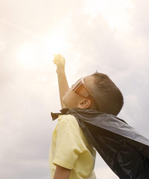 happy kid play superhero , boy power concept